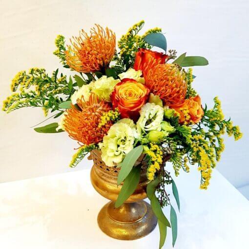 Noto coppa di fiori dai toni arancio